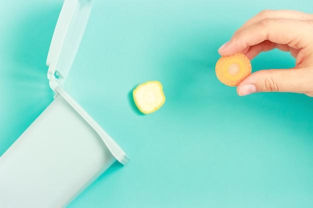 여성의 손은 파란색 배경에 있는 플라스틱 쓰레기통에 음식물 쓰레기를 던집니다.
