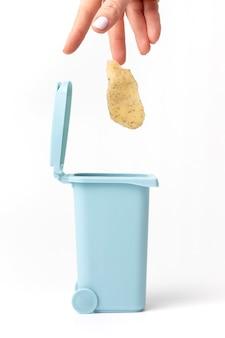 Female hand throws organic trash, potato stub into the trash can on white