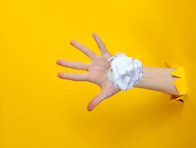 Female hand throws white crumpled ball of paper through the torn yellow paper hole. minimalistic idea concept