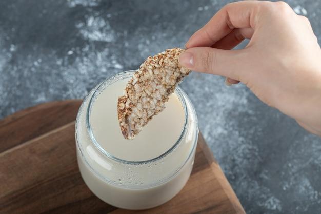 Female hand thrusting rice cake into milk