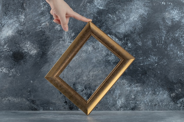Female hand touching picture frame on marble.
