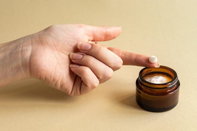 顔のmousturizingクリームでブランド化されていない暗いガラスの瓶に触れる女性の手