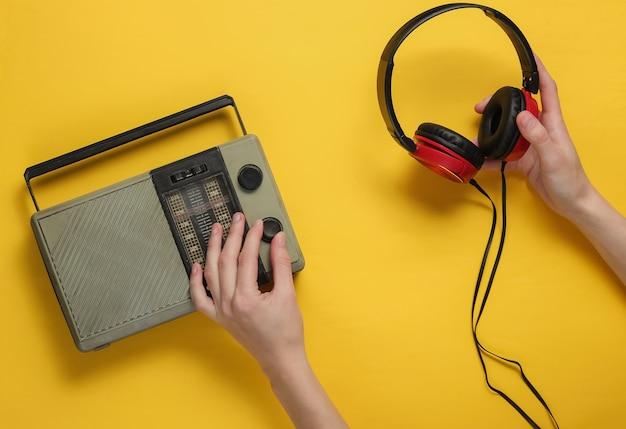 Female hand tunes retro radio receiver and holds headphones