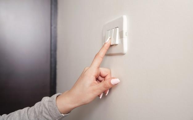 벽에 전기 전등 스위치를 돌리는 여성 손.