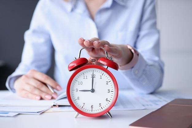 Женская рука выключает красный будильник на рабочем месте крупным планом