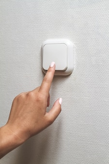 Female hand turns off the light indoors. electrical energy savin