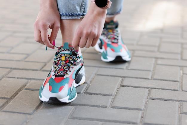 色とりどりのスニーカーのクローズ アップで靴ひもを結ぶ女性の手