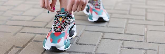 色とりどりのスニーカーのクローズアップに靴紐を結ぶ女性の手
