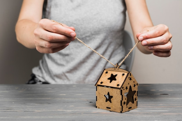 Female hand tying string on handmade brown house