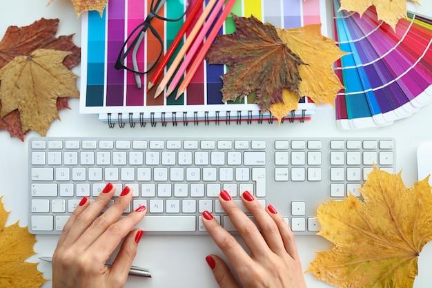 Женская рука типа текстового сообщения с белым keyboar на офисном столе крупным планом