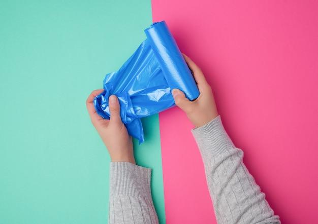 Женская рука разматывает синий полиэтиленовый пакет для мусора
