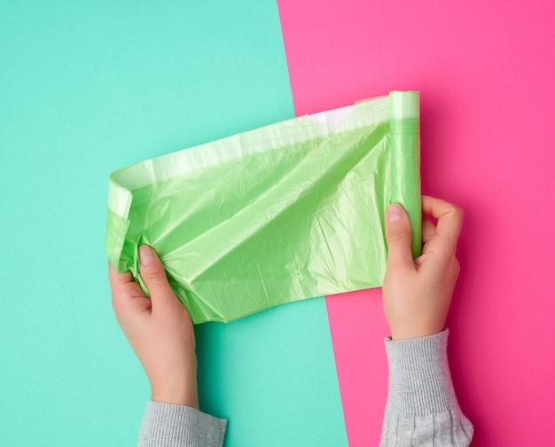 Female hand unwinds a green plastic bag for rubbish