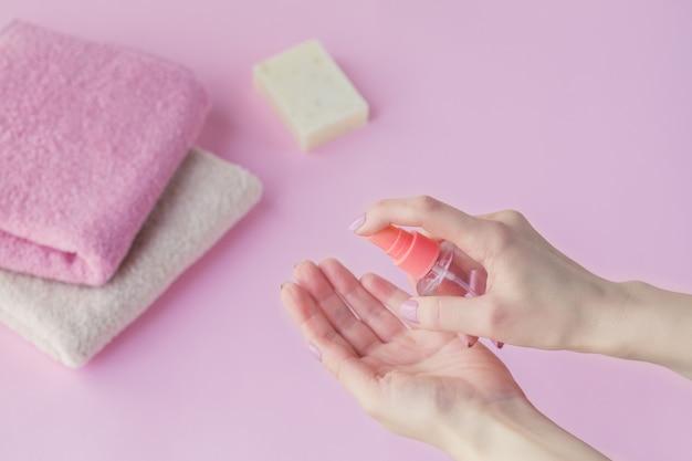 Женская рука используя антибактериальное дезинфицирующее средство для рук на свете - розовой предпосылке.