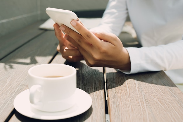 Женская рука с помощью мобильного телефона над деревянным столом в кафе