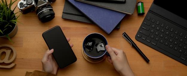 Женская рука с помощью смартфона и держа чашку кофе на деревенский рабочий стол с канцелярскими товарами