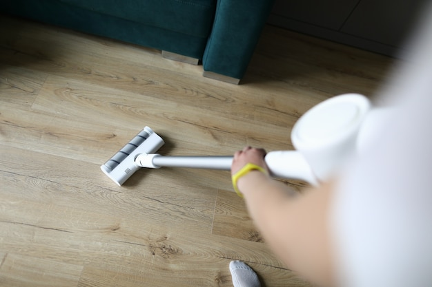Female hand vacuums floor covering in an apartment