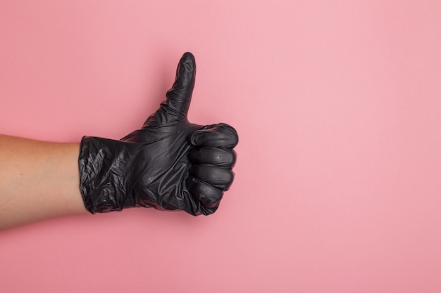 A female hand wearing a black rubber glove is giving thumb up