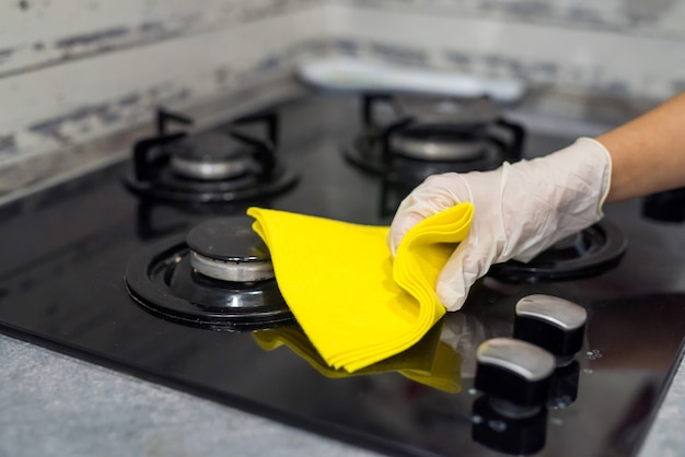 Female hand in white gloves cleaning with a foam gas stove with a glass surface. housework