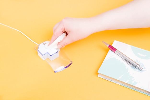 Женская рука вытирает компьютерную мышь влажной тканью, рядом с блокнотом перо на желтой поверхности