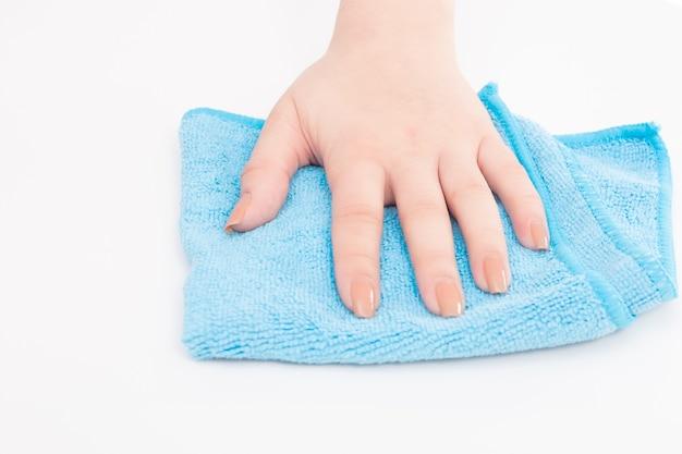 女性の手が青いマイクロファイバークロスで白い表面を拭きます