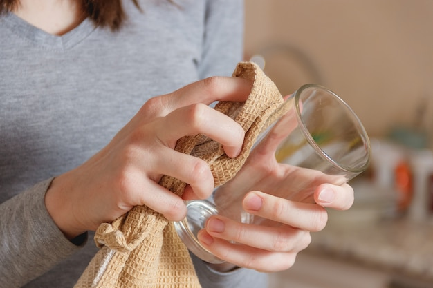 Female hand wipes clean glass by tap in kitchen.