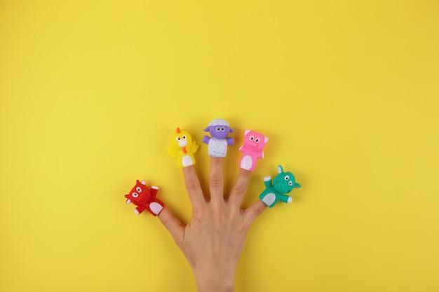 Female hand with 5 finger dolls: cow, sheep, chicken, pig. the concept of child development. place to copy. flat lay.