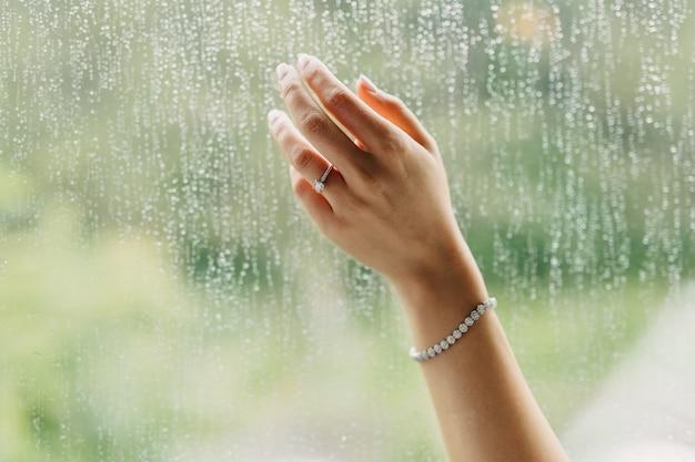 指に婚約指輪を持つ女性の手、雨のしずくでウィンドウに触れる
