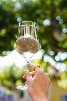 白ワインのグラスと女性の手