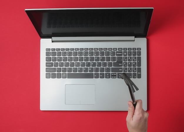Женская рука с молотком ударяет по клавиатуре ноутбука на красном фоне