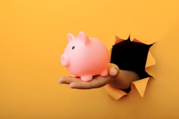 黄色い紙の穴から貯金箱を持つ女性の手。投資と節約。