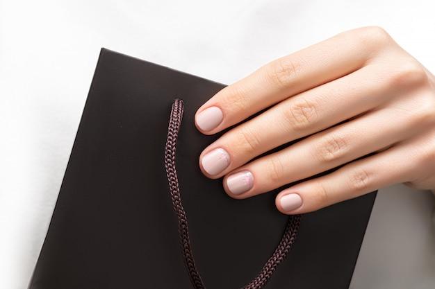 Female hand with beatiful beige nail design hold dark stylish bag on white background