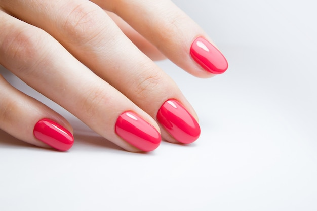赤いジェルポリッシュで美しいマニキュアを持つ女性の手
