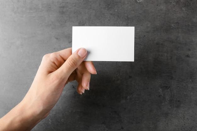 灰色の空白の名刺を持つ女性の手