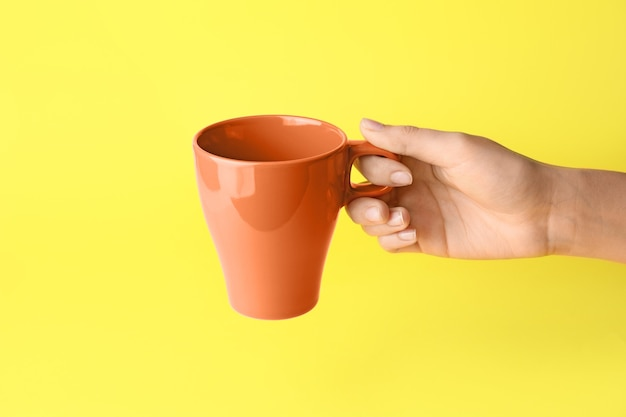 Female hand with blank cup on color surface