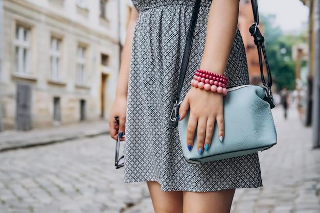 Female hand with blue handbag