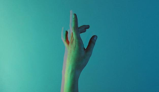 青いホログラフィックカラーライトと女性の手