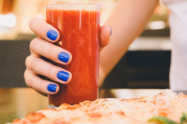 Female hand with blue manicure holding a glass of tomato juice in a pizzeria