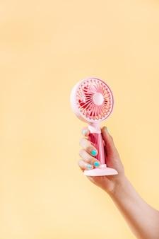 Женская рука с синим лаком для ногтей держит розовый электрический вентилятор на желтом фоне