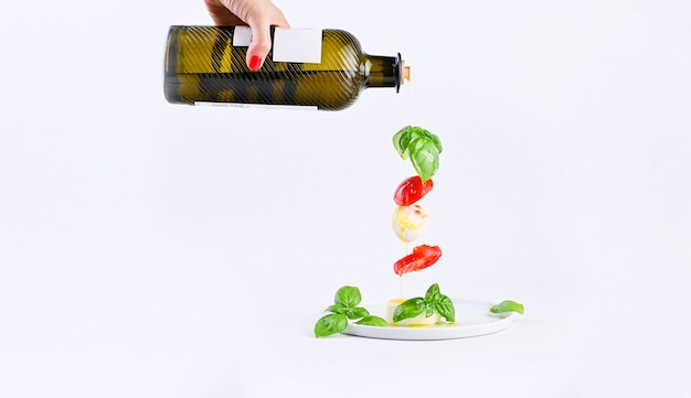 Female hand with bottle of oil and flying salad in the frame. traditional italian caprese salad. tomatoes, mozzarella, basil, olive oil