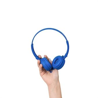 白い表面に分離された明るい青色のヘッドフォンと女性の手