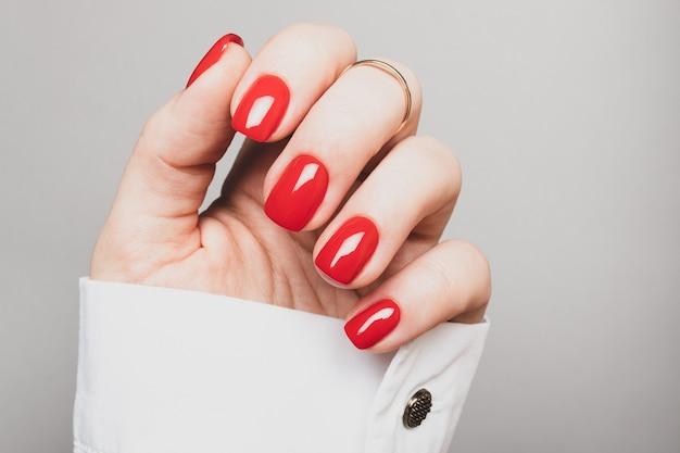 灰色の背景に真っ赤なマニキュアと女性の手