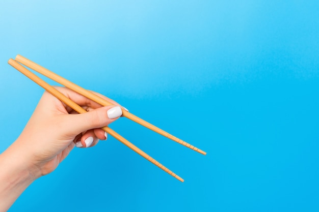 Female hand with chopsticks on blue background. traditional asian food