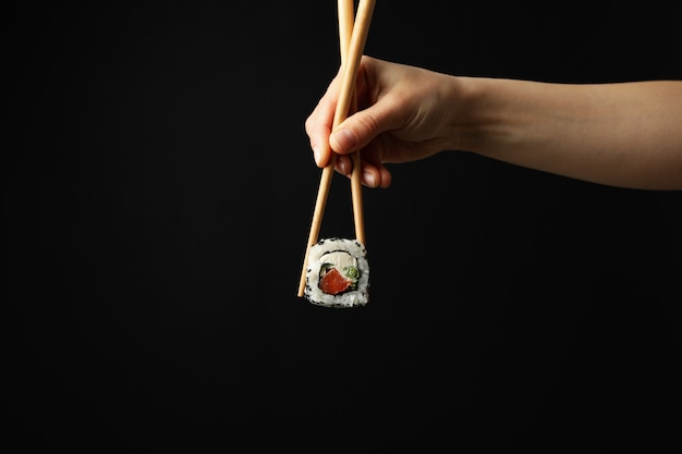 Female hand with chopsticks hold sushi roll on black surface. japanese food