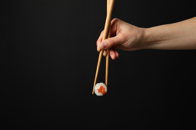 Female hand with chopsticks hold sushi roll. japanese food