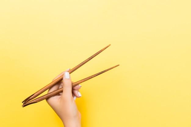 Женская рука с палочками на желтом фоне. традиционная азиатская еда с пустым пространством для вашего дизайна.