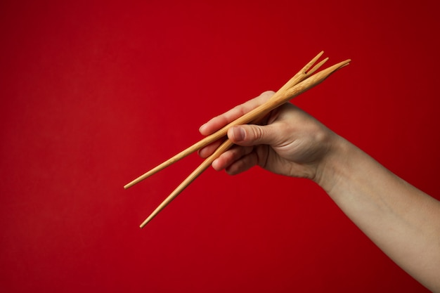 Female hand with chopsticks on red surface