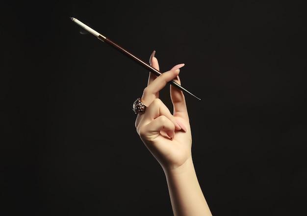 담배 홀더를 가진 여성 손