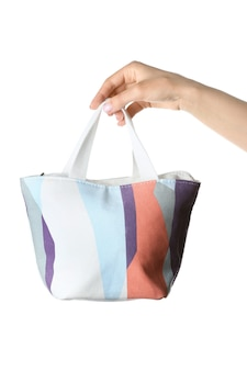 Female hand with cosmetic bag on white