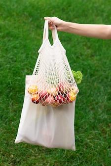 綿のエコバッグを持つ女性の手。廃棄物ゼロのコンセプト
