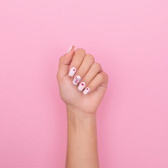 創造的なマニキュアの爪、白いジェルポリッシュ、ハートのデザイン、ピンクの背景の女性の手